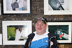 Martin Joyce, IN SIGHT photographer, standing along side two of his photographs at the first IN SIGHT exhibition in Powerscourt Centre.